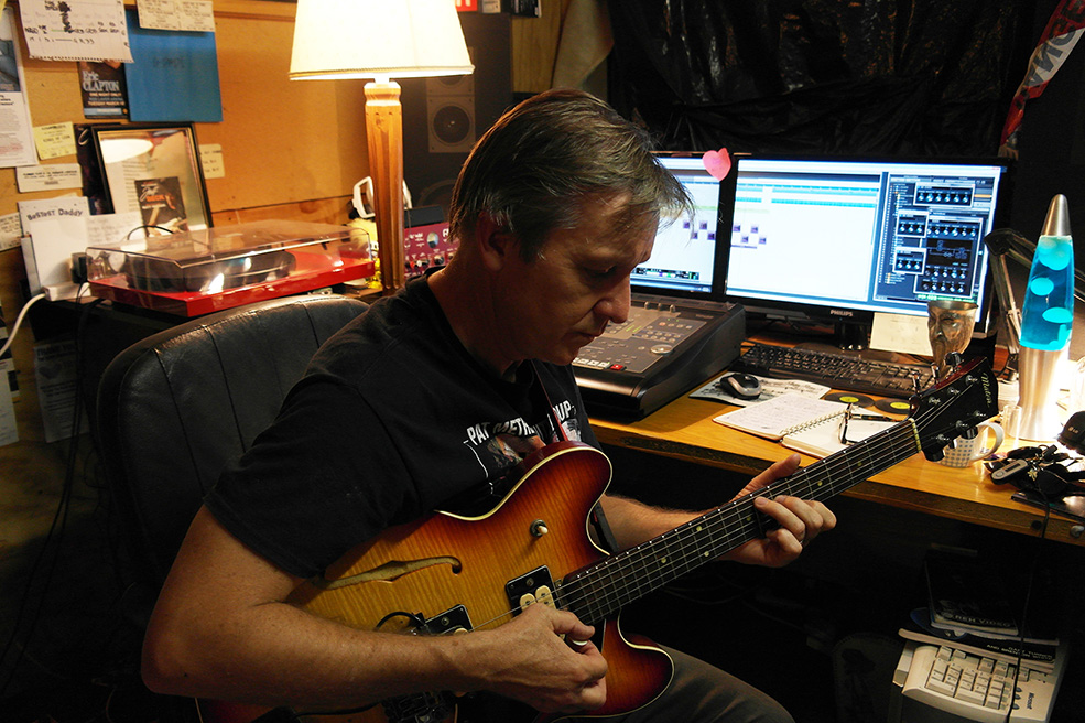 man playing guitar and making music at his home recording studio